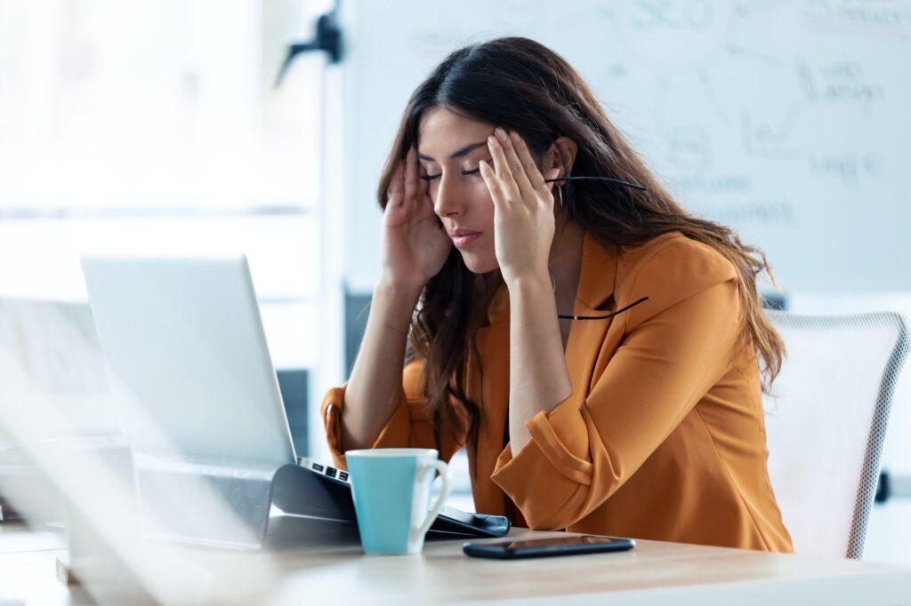 Mujer joven de negocios con dolor de cabeza que trabaja con el ordenador portátil en la oficina.