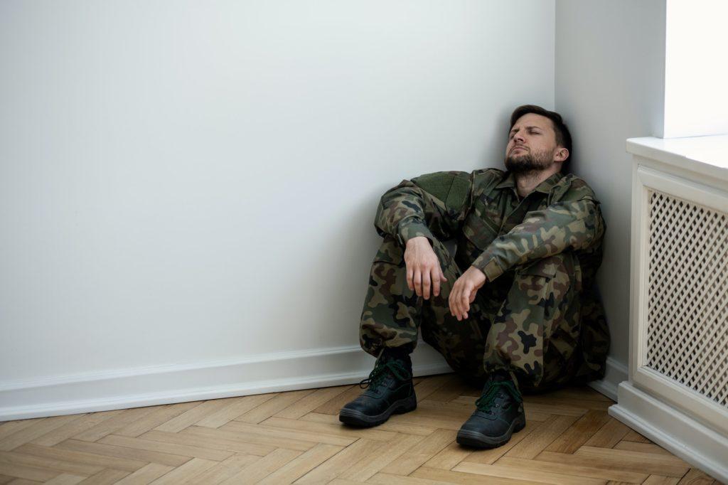Un militar deprimido con uniforme sentado en una esquina de un ro