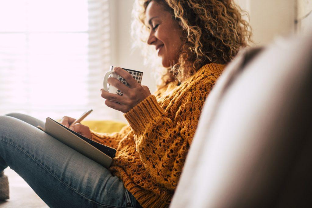 Feliz señora linda en casa escribir notas en un diario mientras que beber una taza de té y relajarse