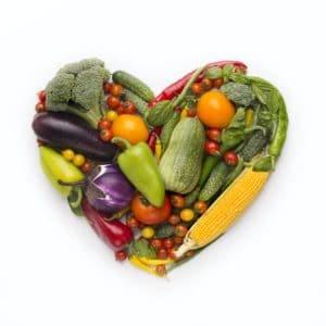 Marco en forma de corazón de verduras frescas sobre fondo blanco