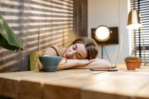 Mujer dormida en el puesto de trabajo en casa